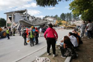 People-and-rescuers-stand-near-collapsed-buildings-following-an-earthquake-in-Amatrice
