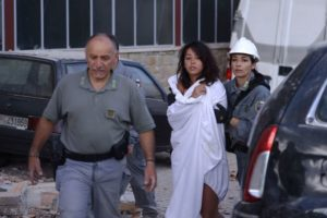 Rescuers-help-a-woman-among-damaged-buil